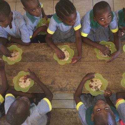 De kinderen genieten van de warme lunch